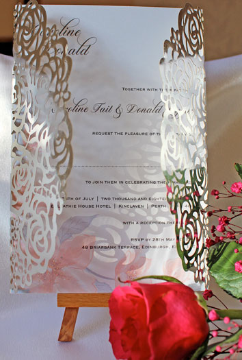 Silver Mirror Roses Laser cut wedding invitation with white pearlescent insert featuring pastel pink and lilac flower corner with glitter highliights