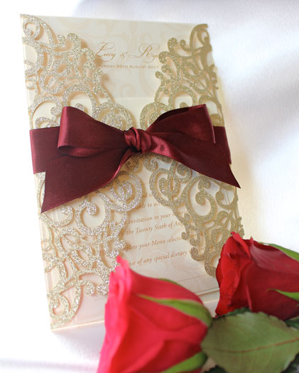 Flair Gold Glitter laser cut wedding invitation tied with burgundy satin ribbon