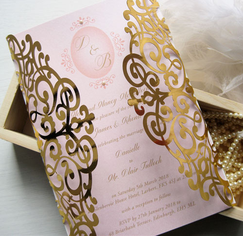 Delicate Flair Gold Mirror laser cut wedding invitation with blush pink insert and pearls and tied with a pink satin ribbon