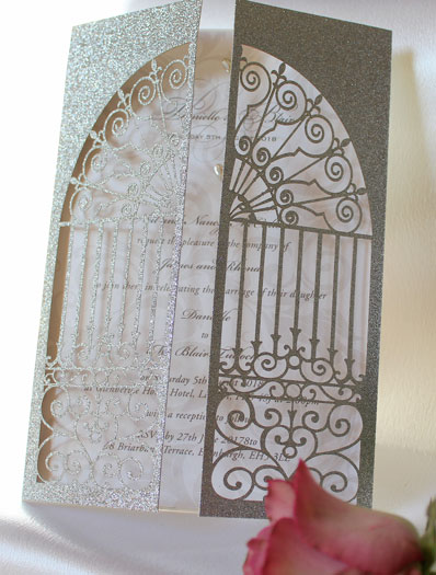 Church Gates laser cut wedding invitation in silver glitter card with white pearlescent insert and two silver metal hearts