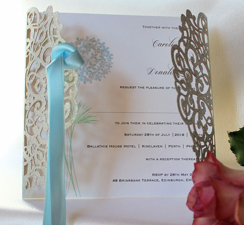 Silver Glitter Swirl laser cut wedding invitation with white pearlescent insert printed with pastel blue and lilac flower