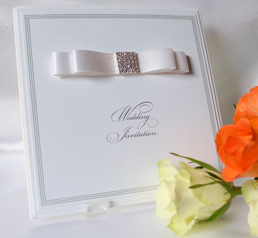 Prague Crystal square bookfold invitation in white with Sparkling square crustl embellishment and double white satin bow
